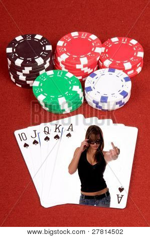 One of the highest hands in poker a Spades Royal Flush on a red felt gaming table with chips in the background with a sexy woman flipping off the looser