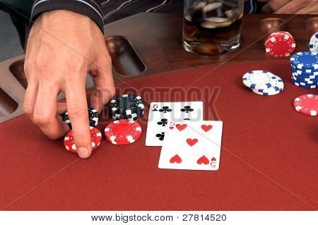 Close up detail of the hand of a man placing a double down bet in a  blackjackgame  in Las Vegas