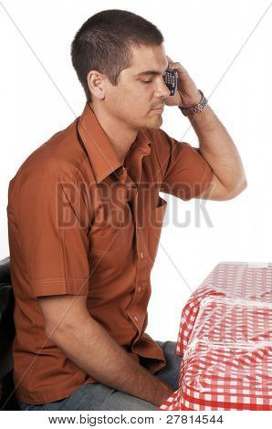 handsome man talking on the cell phone while sitting at a Bistro table