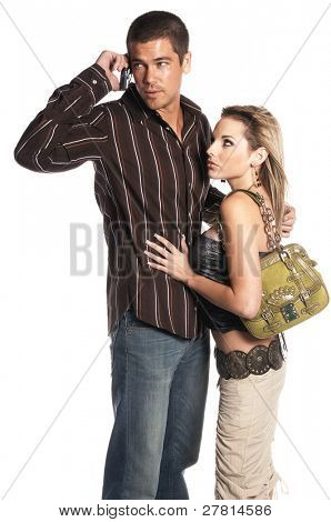Glamorous couple fashionably dressed with the man talking on a cell phone and ignoring the woman