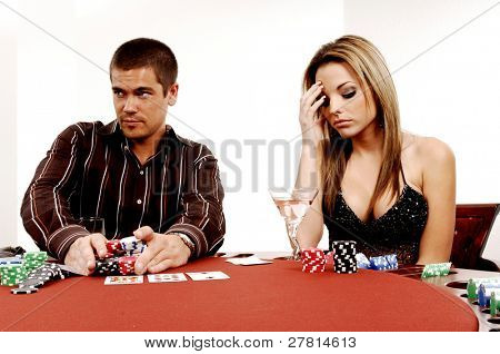 A sexy young couple playing out a hand of Texas Holdum laid out on a casino table Card backs are a digitally created design