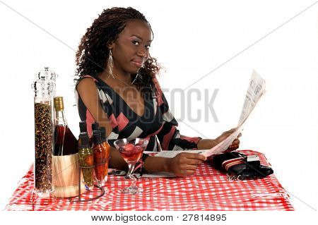 Pretty young African American business woman  enjoying a beverage and a newspaper at a sidewalk Cafe
