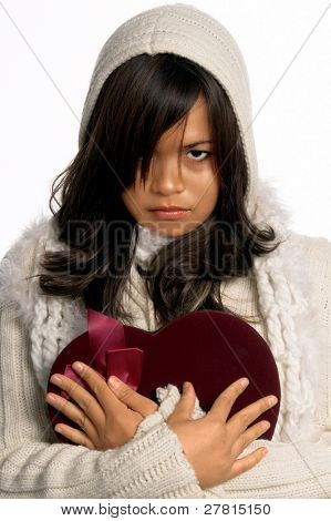 Beautiful but sad young Asian woman  in a heavy sweater and scarf clutching a Valentine to her heart as if it is broken