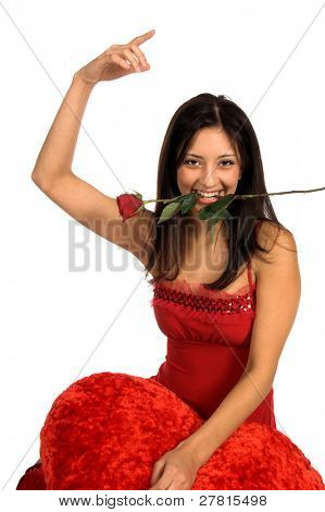 Beautiful latina woman in a red Valentine's Day dress with a red rose clenched in her teeth