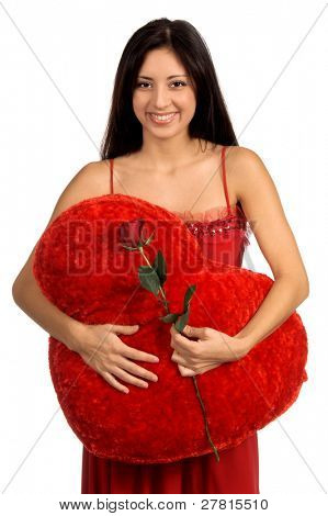 Beautiful latina woman in a red Valentine's Day dress with a red rose a big red heart shape pillow
