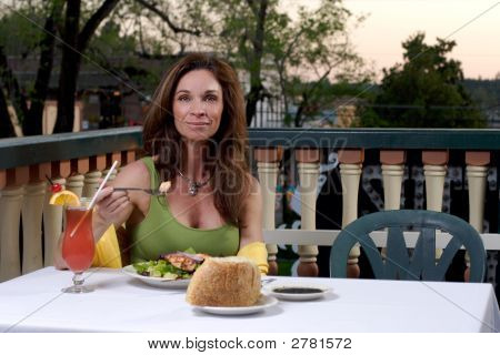 Woman Dining On The Patio