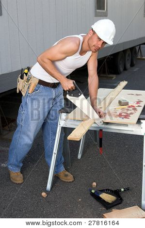 Rugged young construction worker cutting a board with a hand saw