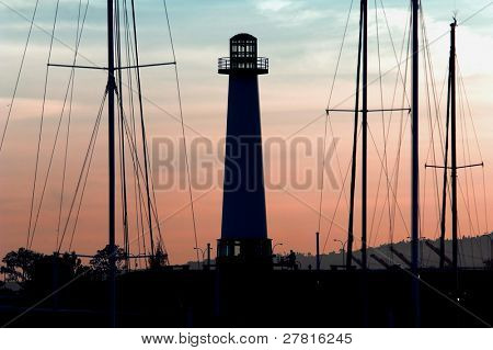 Long Beach Harbor Lighthouse back lit and silhouetted by a Southern California sunset and framed by the tall masts of Sail Boats