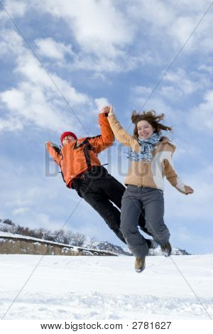 Casal saltar sobre o céu azul no inverno