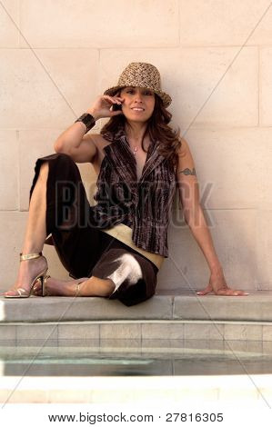 Glamorous young Latina in a fedora sitting in an alabaster courtyard