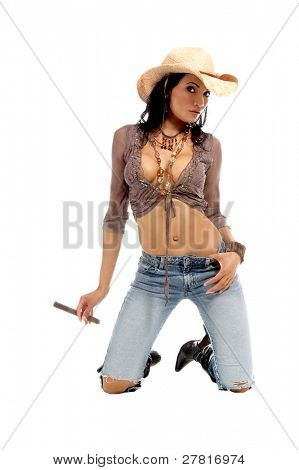 Super sexy rodeo cowgirl in torn jeans, boots and cowboy hat smoking a big cigar