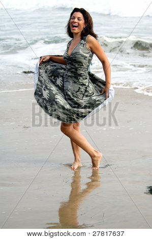 Beautiful Latina woman dancing barefoot on the beach in a camo dress