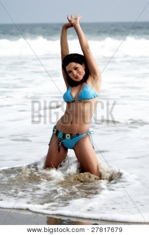 Beautiful Latina woman on the beach in a blue bikini