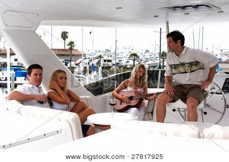 A casual  group of young adults gathered  on a yacht in the harbor with a blond woman playing guitar