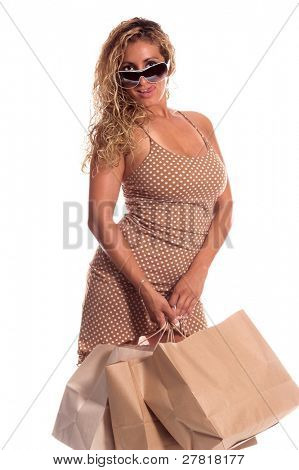 A beautiful Latina woman in a stylish brown dress with white polka dots and white high heels high heels and super model sunglasses out for a day of shopping on the mall. Carrying large shopping bags