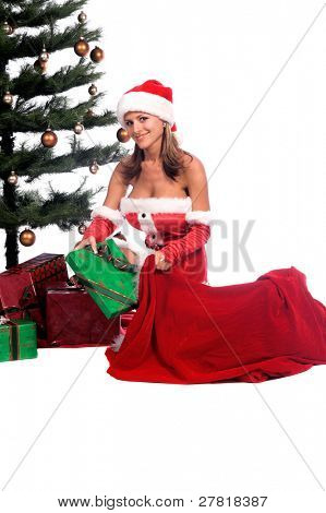 Sexy Ms. Santa Claus unloading Christmas Gifts from Santa's bag and placing them under the tree