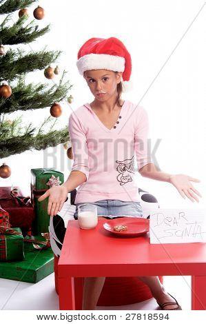 ein junges Mädchen zuckt mit den Schultern und bestreitet, dass sie aß hat die Cookies und Milch, die für Santa Claus bestimmt wurden