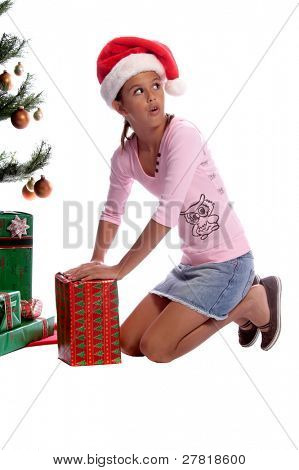 A young girl sneaking and unwrapping a gift under the Christmas tree