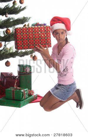 ein junges Mädchen in einem Santa Cap schütteln ein Geschenk unter dem Weihnachtsbaum zu sehen, ob sie, Wha herausfinden können