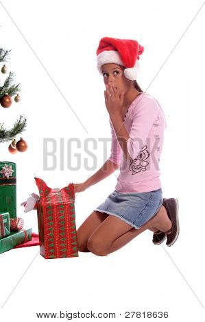 A young girl sneaking and unwrapping a gift under the Christmas tree reacts with surprise as she hears a noise
