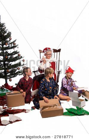 A group of children gathered around the Christmas Tree opening their gifts while Mrs. Santa Claus sits watching from  her rocking chair.