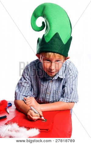 A young boy in an elf hat working on a Christmas craft project of decorating a stocking