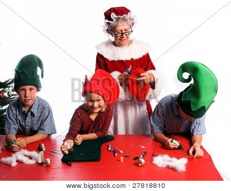 A group of young children aged 6 - 12 wearing elf hats and working with Mrs. Santa Claus on a Christmas craft project of decorating a stocking