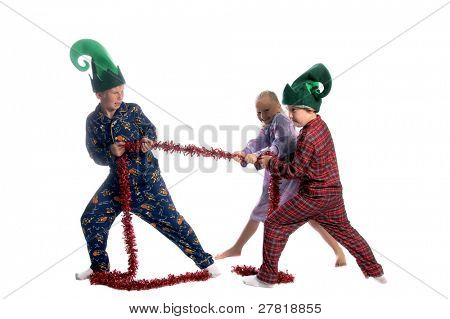 Young children in their pajamas and elf hats having a tug o war with a Christmas garland the two young ones are against the one older boy