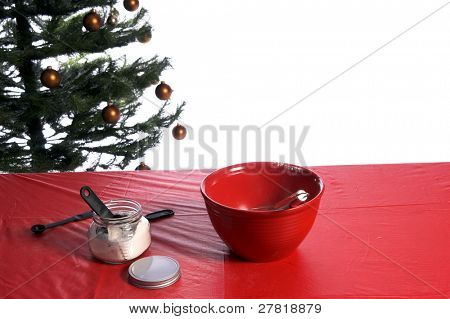 A mixing bowl, whisk, jar of flour and assorted kitchen utensils on a table in front of a Christmas tree ready for someone to come along and make some cookies
