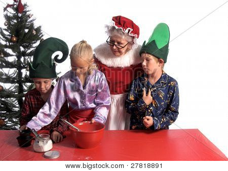 A group of young children aged 6 - 12 wearing elf hats and pj's baking cookies with Mrs. Santa Clause