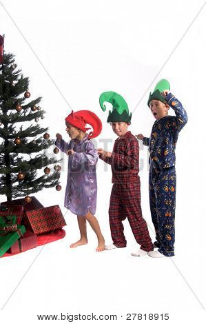A group of sleepy children stretch and yawn as they make their way to the Christmas tree on Christmas morning.