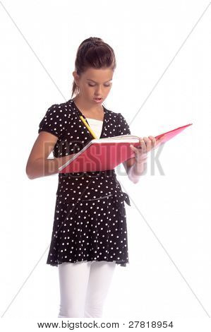 Pretty young girl (11 years old) in a black and white Polka dot dress and white leggings writing notes in a journal