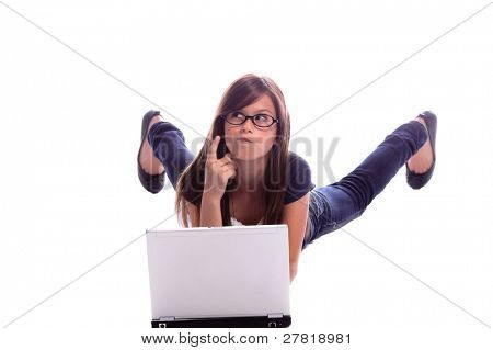 Young girl laying on her belly on the floor thinking and doing her homework on a laptop computer