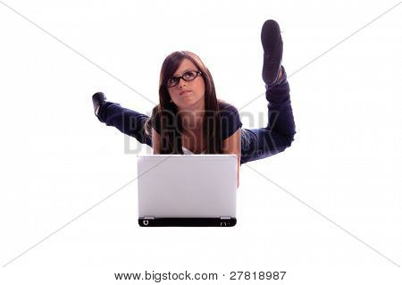 Young girl laying on her belly on the floor doing her homework on a laptop computer