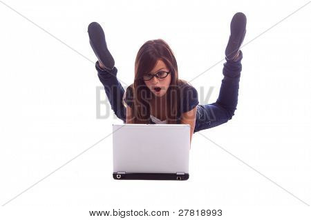 Young girl laying on her belly on the floor and shocked by what she sees on her laptop computer screen.
