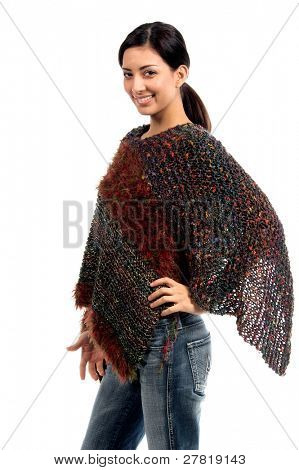 Right profile of a beautiful young Mexican woman in a couture poncho / shawl of multicolored yarns with her left hand on her hip
