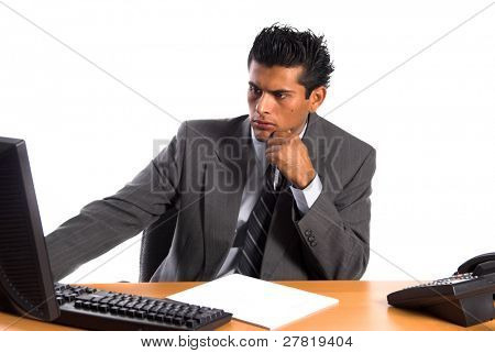 Handsome young Hispanic business man in a grey suit at his desk intently studying his computer monitor