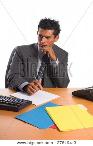 Handsome young Hispanic business man in a grey suit at his desk intently studying his computer monitor and making notes on a pad of paper