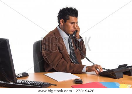 Handsome young Hispanic business man making a phone call in his office