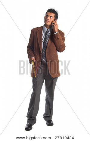 Handsome young Hispanic business man in a brown suit sans coat standing at his desk and talking on his cell phone