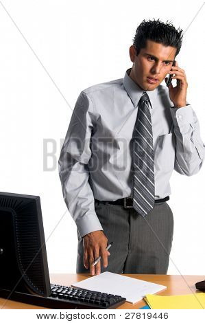 Handsome young Hispanic business man in a grey suit sans coat standing at his desk and talking on his cell phone