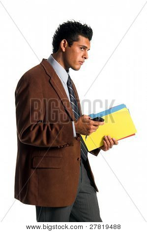 Handsome young Hispanic business man in looks to the camera dialing his cell phone while holding some file folders
