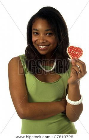Beautiful young black woman smiling and about to take a bite from a heart shaped Valentine's Day cookie