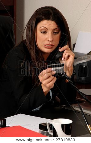 Business woman on her office phone making a payment with a credit card