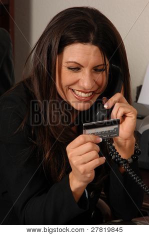 Happy business woman on her office phone making a payment with a credit card