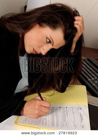 Female executive reading and preparing to fill out tax forms while sitting at her desk