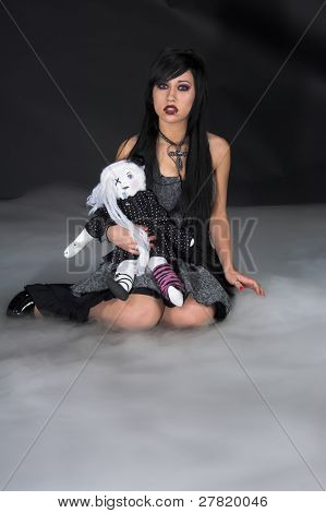 Beautiful raven haired Gothic Vampire girl in a black and grey dress with a rag doll and sitting in a nighttime fog.