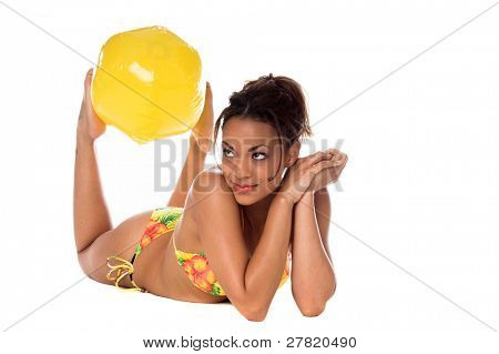 African American fashion model in a yellow tone tropical pattern bikini laying one her belly with a beach ball between her feet