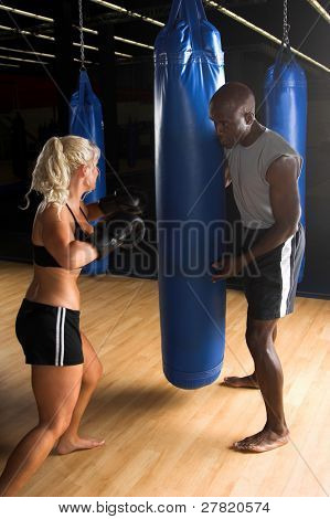 Beautiful but dangerous female fighter working with her trainer punching a heavy bag in an Mixed Martial Arts gym.