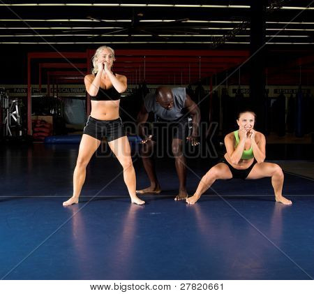 Young female MMA fighters doing power squats in the gym with their trainer.  Focus on on the right in a deep squat